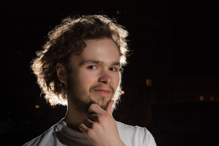 Portrait of young man outdoors with black background and light behind him