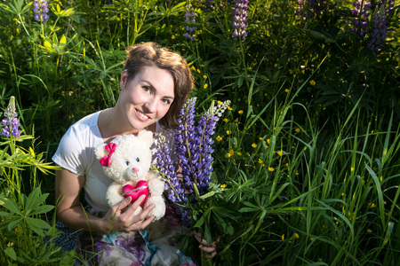 Beautiful girl in a field of purple lupines in a summer day