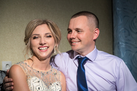 Beautiful bride in white dress and groom in the room before wedding ceremony