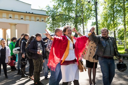 Kirov, Russia - June 15, 2018: Unusual wedding couple including bride and groom in rocker leather jacket in the city street with their friends