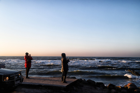 Svetlogorsk, Russia - April 02, 2018: People taking picture near sea during sunset in a cold spring evening