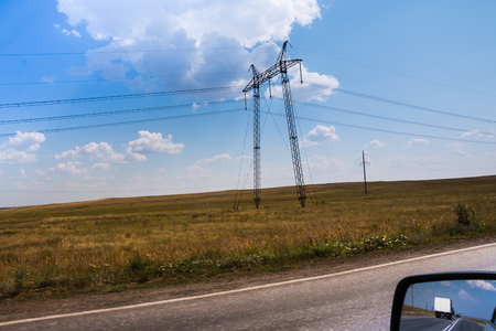 High voltage lines and agricultural landscape on a sunny day with white clouds in the blue sky. Taking photos from a moving car with blurring the edge of the field Standard-Bild