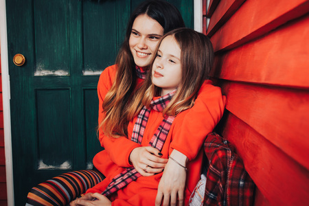 Two girls are sisters in red sweaters and striped scarves relax and have fun in a beautiful room, decorated for Christmas and the New year