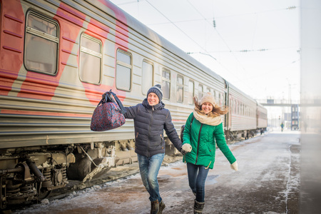 Couple is late for the train at railway station in a cold winter day