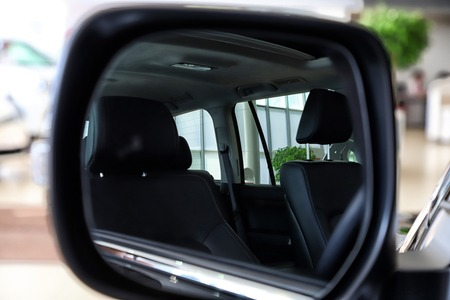 Car mirror and the reflection in it of the interior of the car in a day