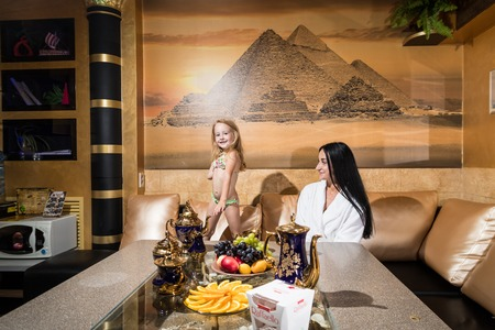 Mother and girl in a beautiful room at the table. Family has rest in the sauna