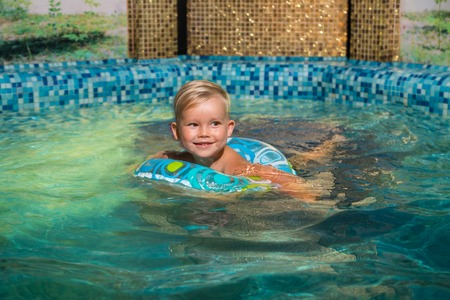 Nice child swiming in blue small pool. Boy have fun in water indoors