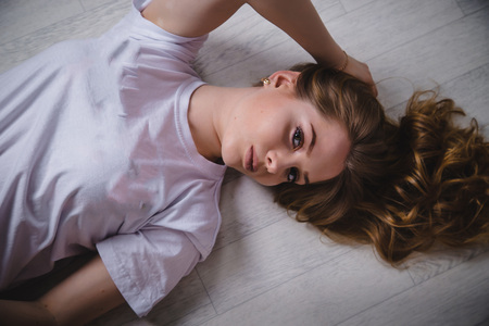 Girl in a white t-shirt with long hair lying on the white floor Stock Photo