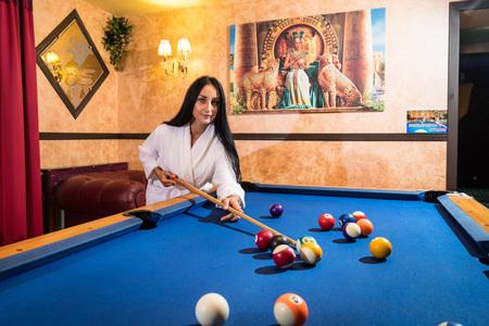 Beautiful sexy girl in bikini near pool table in beautiful room in Egyptian style. Game of billiards