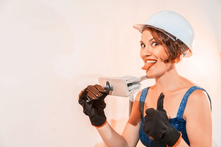 Sexy cute girl who is builder, painter, worker being in a renovated room