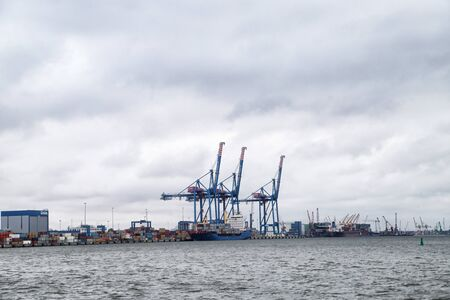 Klaipeda, Lithuania - April 02, 2018: Cargo ship-lifting cranes in the harbor and cloudy sky background