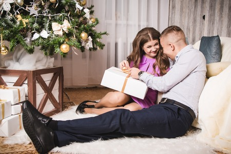 Nice couple in the room with the decorated Christmas tree Stock Photo