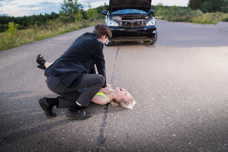 Man strangling a girl on the road for a broken car. Photoshoot