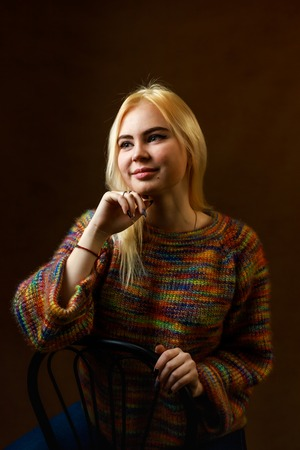 Portrait of the beautiful sexual girl. Blonde young woman in motley sweater. Picture in low key