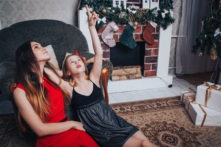 Two girls sisters have relax and fun in a nice room decorated for Christmas and the New year