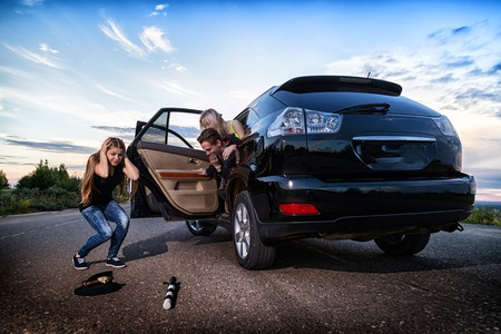Girl near the car looking with horror at the cap and baton of a police officer on the road. Female driver hiting a COP. Photoshoot in Russia Stock Photo