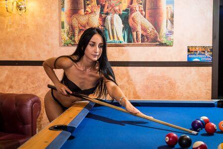 Russia, Kirov - June 18, 2018: Beautiful sexy girl in bikini near pool table in beautiful room in Egyptian style. Game of billiards