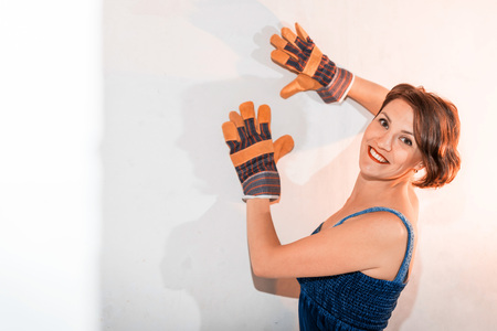 Sexy cute girl who is builder, painter, worker being in a renovated room. Hands in gloves