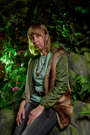 Girl in a green jacket with blond hair near an artificial rock with a grotto. Fabulous photo shoot in the Studio Imagens