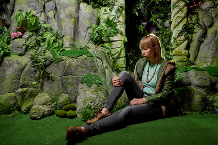 Girl in a green jacket with blond hair near an artificial rock with a grotto. Fabulous photo shoot in the Studio. Elf near his house. Dark key
