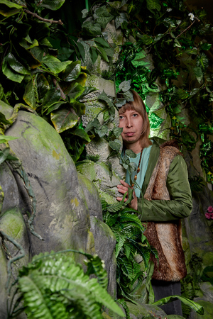 Girl in a green jacket with blond hair near an artificial rock with a grotto. Fabulous photo shoot in the Studio. Elf near his house. Dark key Фото со стока