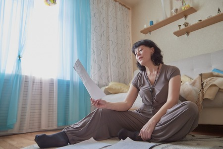 Nice middle-aged woman in the living room. Lady at home with a paper in a day. Female poet reading poetry Stock Photo