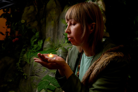 Girl in a green jacket with blond hair with a small candle in her hands near an artificial rock with a grotto. Fabulous photo shoot in the Studio. Elf near his house. Dark key