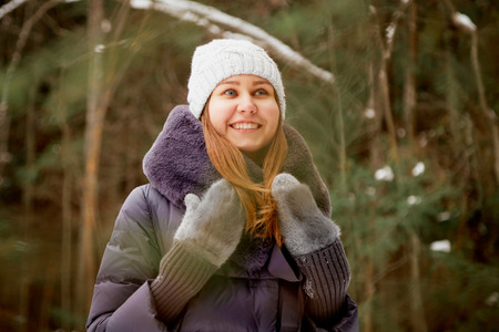 Portrait of a girl in a pine forest on a winter day