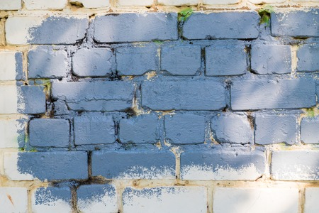 Texture of the wall for background. Roughness and irregularity. Stain of blue paint on the brick
