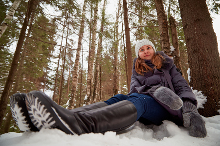 Girl in a pine forest on a winter day. Single walk