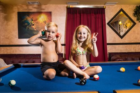 Kirov, Russia - July 18, 2018: Cute children sitting on the billiards table and balls arround. Barefoot kids. Boy and girl, brother and sister, friens have fun together during photosoot Redactioneel