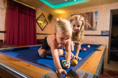 Kirov, Russia - July 18, 2018: Cute children sitting on the billiards table and balls arround. Barefoot kids. Boy and girl, brother and sister, friens have fun together during photosoot Stockfoto - 143352729