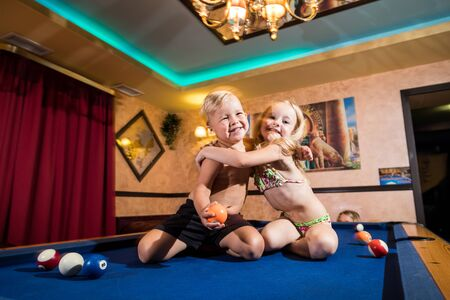 Kirov, Russia - July 18, 2018: Cute children sitting on the billiards table and balls arround. Barefoot kids. Boy and girl, brother and sister, friens have fun together during photosoot Stockfoto - 143352730
