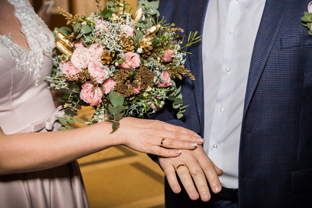 Bride and groom wear rings during the marriage ceremony in registry office