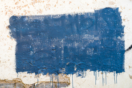 Texture of the wall for background. Roughness and irregularity. Uneven rectangle of blue paint