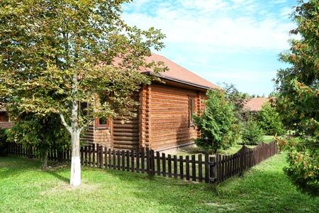 Pequeña casa de madera en jardín con árboles. Bonito paisaje de verano Foto de archivo