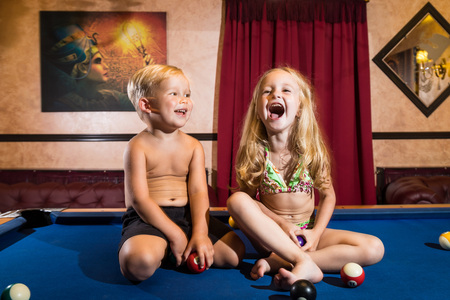 Kirov, Russia - July 18, 2018: Cute children sitting on the billiards table and balls arround. Barefoot kids. Boy and girl, brother and sister, friens have fun together during photosoot