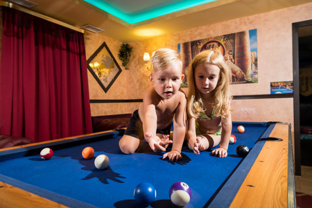 Kirov, Russia - July 18, 2018: Cute children sitting on the billiards table and balls arround. Barefoot kids. Boy and girl, brother and sister, friens have fun together during photosoot Stockfoto