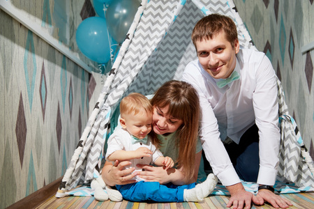 Couple with baby playing in the room. Mom, dad and son together. Photoshoot at home Stock Photo