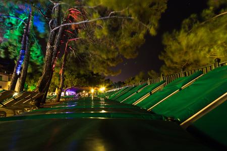 Empty sunbeds with umbrellas at dark night. Close up concept