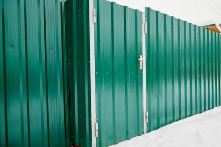 Door in the metal fence in winter day and snow arround