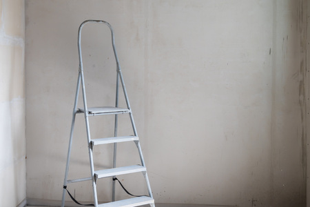 Weiße Aluminium-Stufenleiter im Zimmer mit weißen Wänden