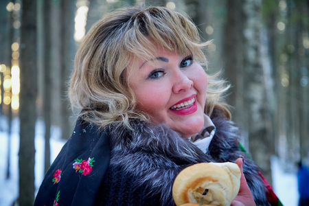 Portrait of beautiful plump woman in a nice winter forest full of snow. Lady in the bright shawl with red flowers. Russia