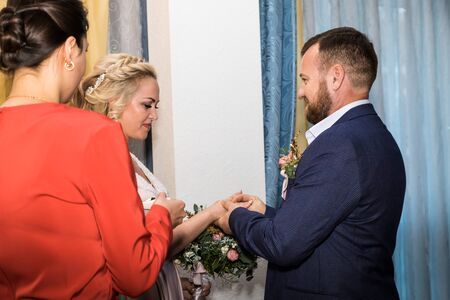 Kirov, Russia - October 12, 2018: Bride and groom wear rings during the marriage ceremony in registry office Редакционное
