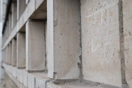 Texture of the wall for background. Roughness and irregularity. Building material brick. Columns. The view from the side