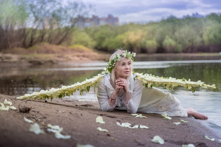 Nice blonde girl with white flower wings on the beach near river in cloudy day