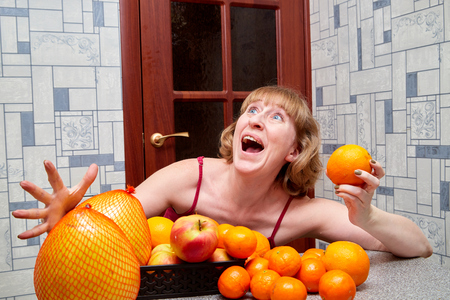 Middle-aged woman with fruit at the table in the room Stockfoto