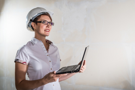 Cute nice young woman in white construction protection building helmet and unfinished apartment in the background. Female architect, desigher or engineer. New resident in an unfinished room Stock Photo