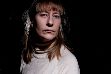 Portrait of a middle-aged sad blonde woman in the room. Photoshoot in a dark key