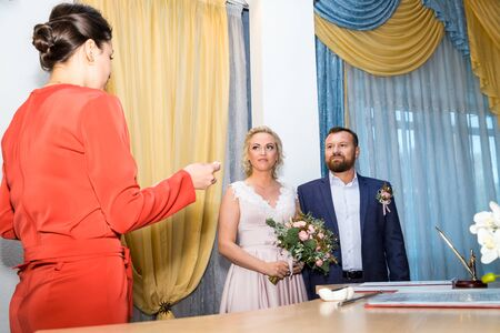 Kirov, Russia - October 12, 2018: Bride and groom signing marriage wedding certificate at registry